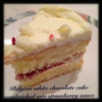 Belgian White chocolate cake sandwiched wiv strawberry sauce