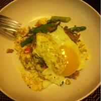 Scrambles eggs with ground turkey, tomatoes, asparagus, and a sunny side up egg on top