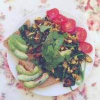 Tofu scramble with shiitake, onion and spinach, avocado on toast and tomatoes on the side, topped with cilantro