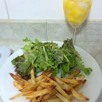 Oven-baked peri-peri fries with greens and a glass of wine cooler