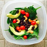Spinach salad with avocado, beans, tomatoes, and cashews