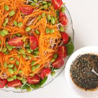 Japanese inspired salad with ramen, edamame, carrot, tomato, baby spinach with a black sesame dressing