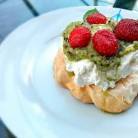 Mini pavlova topped with freshly whipped cream, fresh strawberries and a kiwi puree