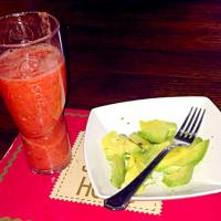 Strawberry and orange smoothie with sliced and salted avocado