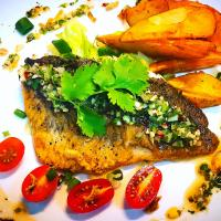 Pan fried seabass with chimichurri, sour lettuce salad and potato wedges.